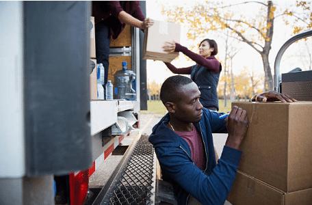 personnes qui mettent des cartons dans un camion de déménagement