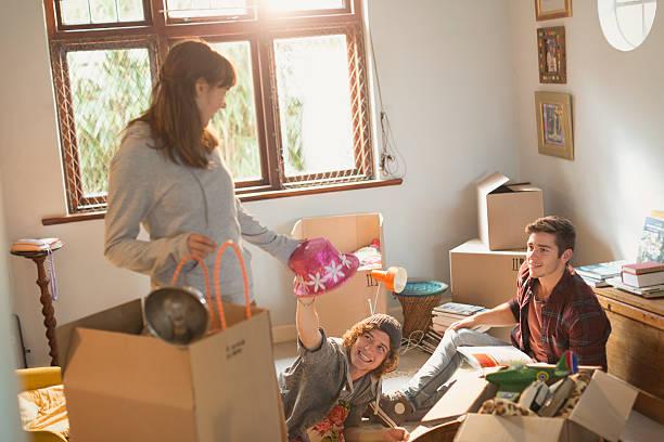 Groupe d'amis en train de préparer des cartons de déménagement dans un appartement