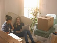 Deux jeunes colocataires qui déménagent dans leur nouvel appartement rempli de cartons